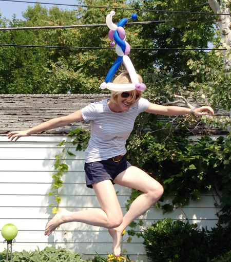 Photo of Heather B. Armstrong mid-air as she jumps on a trampoline wearing a hat sculpted from balloons.